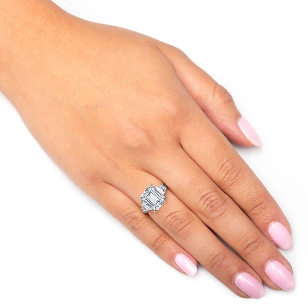 hand with emerald diamond ring